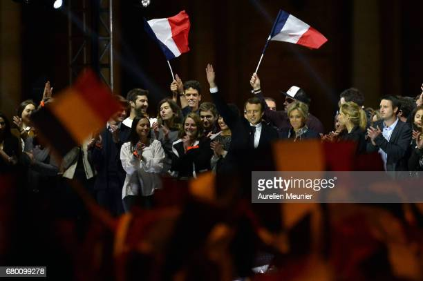 Emmanuel Macron and his wife Brigitte Macron salute voters after his speech as he celebrates his Presidential election victory At Le Louvre In Paris...