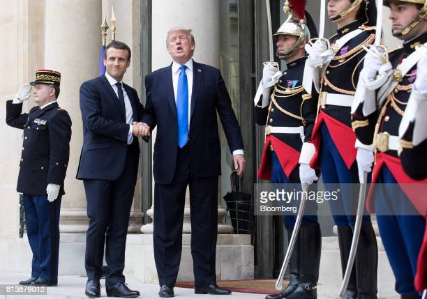 Emmanuel Macron France's president center left and US President Donald Trump center right shake hands while posing for photographs at the Elysee...