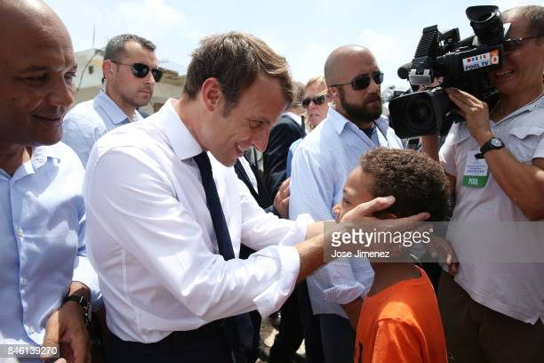 Emmanuel Macron President of France greets twelve year old Tyson Labardu during his visit after the passing of Hurricane Irma on September 12 2017 in...