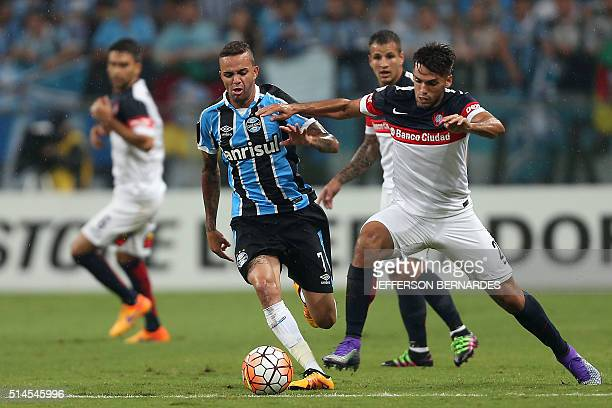 Emmanuel Mas of Argentina's San Lorenzo vies for the ball with Luan of Brazil's Gremio during their Copa Libertadores football match at Arena do...