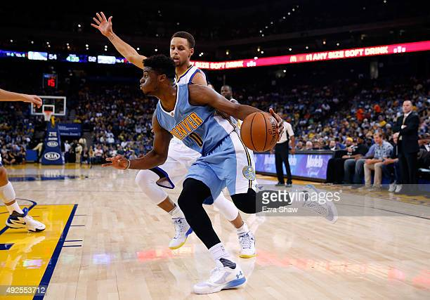 Emmanuel Mudiay of the Denver Nuggets dribbles past Stephen Curry of the Golden State Warriors at ORACLE Arena on October 13 2015 in Oakland...