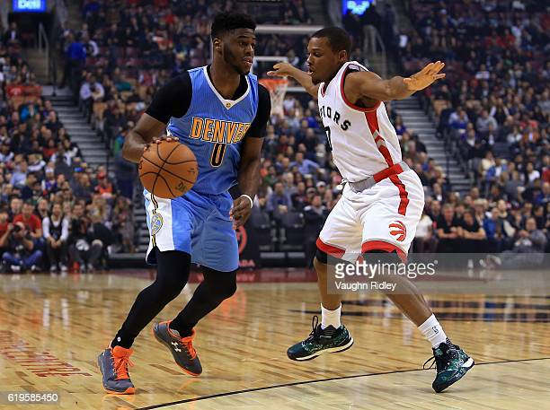 Emmanuel Mudiay of the Denver Nuggets dribbles the ball as Kyle Lowry of the Toronto Raptors defends during the first half of an NBA game at Air...