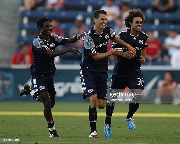 Emmanuel Osei Marko Perovic and Kevin Alston of the New England Revolution celebrate Perovic's gamewinning goal over the Chicago Fire during a...