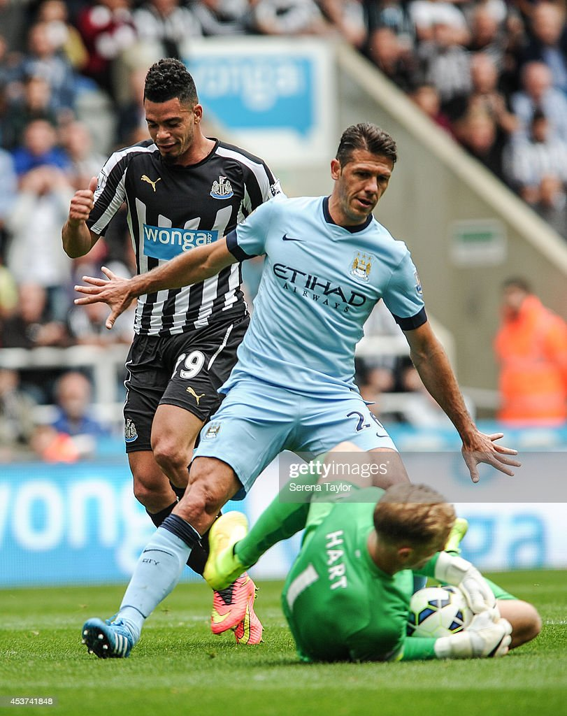 Emmanuel Riviere of Newcastle is beaten to the ball by Manchester City Goal Keeper Joe Hart and Martin Demichelis (26) during the Barclays Premier League match between Newcastle United and Manchester City at St.James' Park on August 17, 2014, in Newcastle upon Tyne, England.