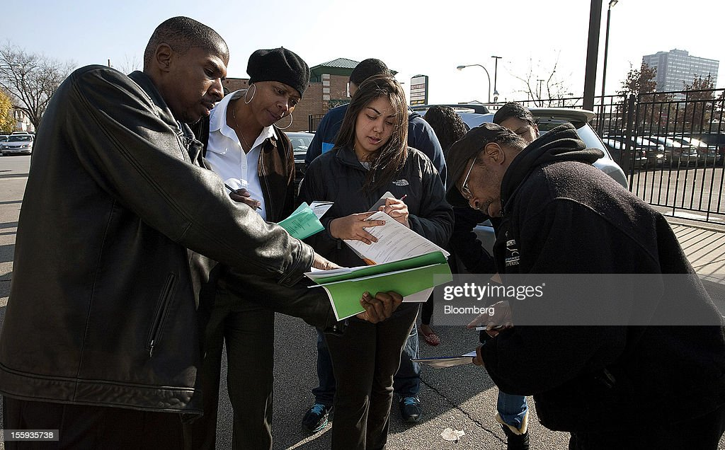 Emmanuel Stewart, left, gives job seekers standing in line information about the City of Chicago job fair at Kennedy King College in Chicago, Illinois, U.S., on Friday, Nov. 9, 2012. The U.S. Department of Labor is scheduled to release initial jobless claims data on Nov. 15. Photographer: Frank Polich/Bloomberg via Getty Images