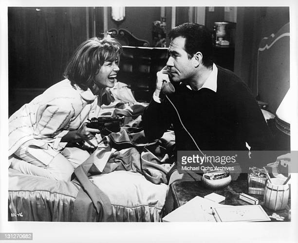 Emmanuele Riva laughing while Ugo Tognazzi is on the phone in a scene from the film 'The Hours Of Love' 1963