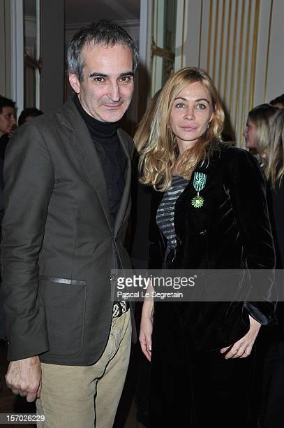 Emmanuelle Beart poses with Director Olivier Assayas after being honored the Officier des Arts et des Lettres at Ministere de la Culture on November...