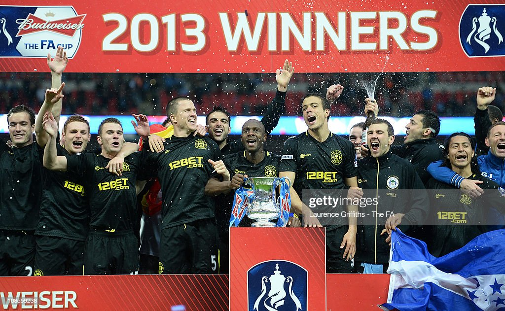 Emmerson Boyce of Wigan Athletic celebrates with team mates as he lifts the trophy after victory in the FA Cup with Budweiser Final match between Manchester City and Wigan Athletic at Wembley Stadium on May 11, 2013 in London, England.
