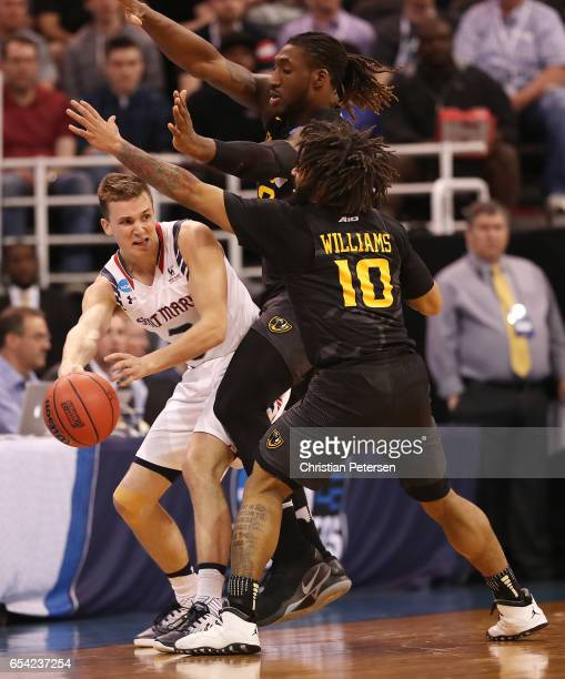 Emmett Naar of the St Mary's Gaels is defended by Mo AlieCox and Jonathan Williams of the Virginia Commonwealth Rams during the first round of the...