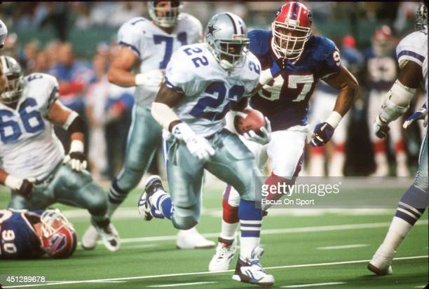 Emmitt Smith of the Dallas Cowboys carries the ball pursued by Cornelius Bennett of the Buffalo Bills during Super Bowl XXVIII on January 30 1994 at...