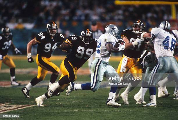 Emmitt Smith of the Dallas Cowboys carries the ball while pursued by Levon Kirkland of the Pittsburgh Steelers during Super Bowl XXX on January 28...