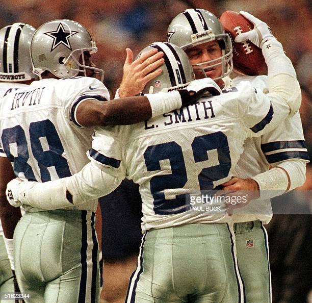 Emmitt Smith of the Dallas Cowboys receives congratulations from teammates Michael Irvin and Troy Aikman after breaking the NFL career touchdown...