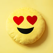 Emoji as soft yellow pillow. Close up. Pattern