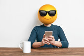 Emoji Head Woman sitting at the desk. Woman wearing a smiling face with sun glasses emoji masks while looking at her phone.This emoji is either enjoying the sun or making cool look extremely natural a