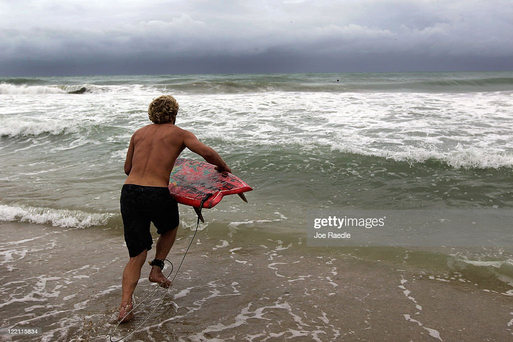 Emory Blair takes to the ocean with his surfboard to take advantage of the waves created by Hurricane Irene as it passes off the coast on August 25, 2011 in Fort Lauderdale, Florida. Irene is moving over the Bahamas and could still be a major storm as it approaches the North Carolina coast the morning of August 27.