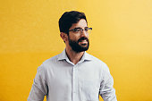 Emotion, portrait, businessman with a beard in glasses on a yellow background.