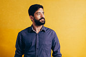Emotion, portrait, businessman with a beard on a yellow background