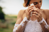 Beautiful bride in white dress weeps tears of happiness on the wedding day. Emotional woman in wedding gown wipes the tears with tissue paper.