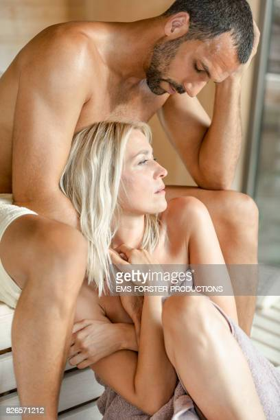 emotional love couple sitting very close together and embrace each other inside a outdoor sauna while enjoying the heat, harmony, detoxing and sweating far away from home