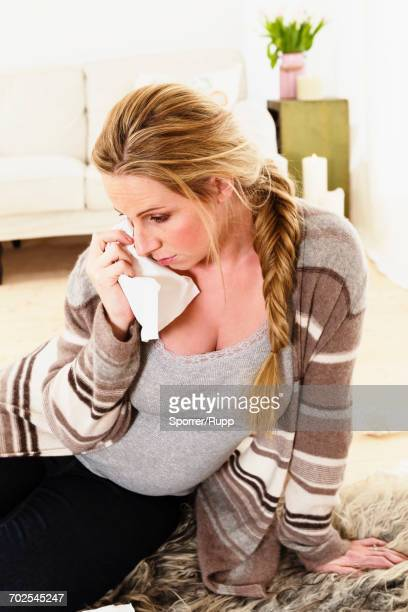 Emotional pregnant woman sitting on floor weeping