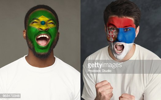 Emotional soccer fans with painted flags on faces : Stock Photo