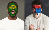 Emotional soccer fans with painted Brazil and Serbia flags on faces. Confrontation of football team supporters from rival countries, sport event, faceart and patriotism concept.