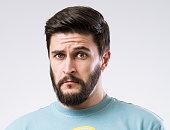 Portrait of surprised doubtful bearded man