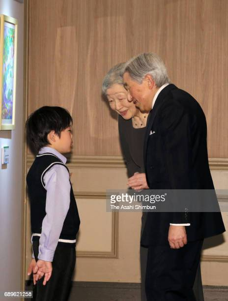 Emperor Akihito and Empress Michiko talk to a children who is a laureate of the national greenery campaign poster contest on May 27 2017 in Toyama...