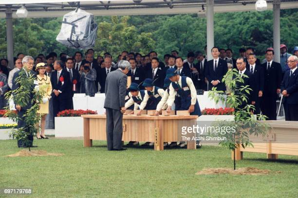 Emperor Akihito casts seed with children during the 46th National Tree Planting Festival at the Central Forest Park on May 21 1995 in Hongo Hiroshima...