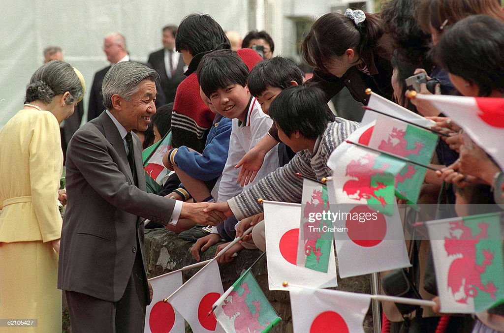 Emperor Akihito Of Japan And His Wife Empress Michiko Shaking Hands With Children Who Have Gathered To Greet Them At Cardiff Castle, Wales.