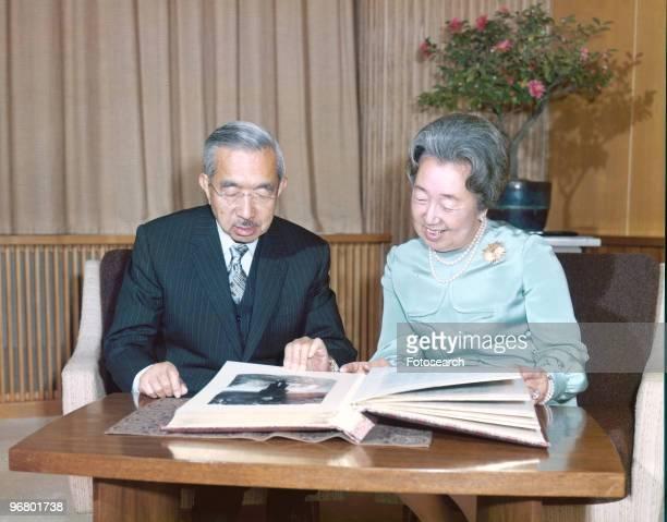 Emperor Hirohito and wife Empress Kojun sit looking over family photo album circa 1950s