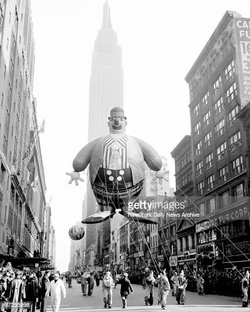 Empire State Building forms a background for this heliumfilled clown floating along 34th Street in Macy Parade