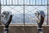 New York - September 10, 2016: Empire State Building observation deck with two binoculars in a sunny day in New York. From 1931 was the tallest world's building for 40 years.