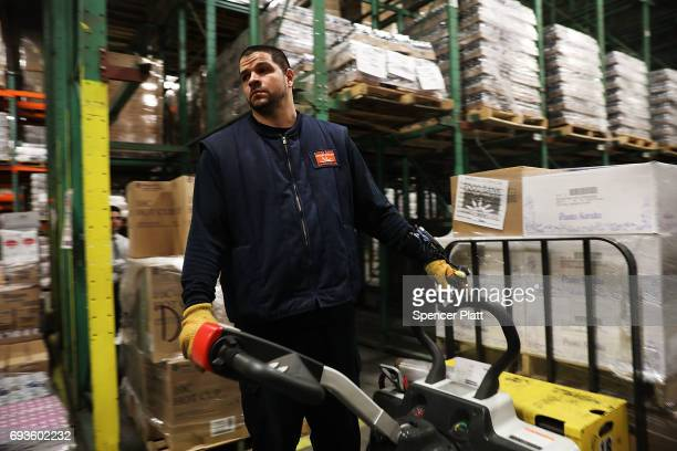 Employee Aaron Torres moves pallets of food at the Food Bank for New York City's main warehouse in the Bronx neighborhood of Hunts Point on June 7...