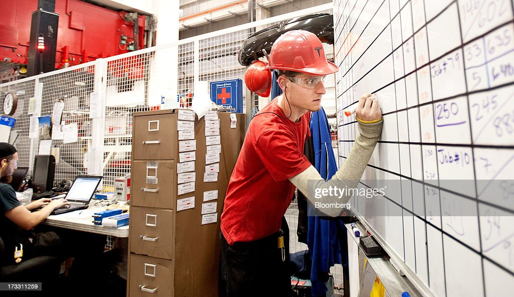 Employee Albert Ghiorso writes downtime figures for a stamping press at Telsa Motor Inc.'s assembly plant in Fremont, California, U.S., on Wednesday, July 10, 2013. Tesla, is building Model S electric sedans faster than its initial 400-a-week goal as demand and the companys production skills increase, Chief Executive Officer Elon Musk said. Photographer: Noah Berger/Bloomberg via Getty Images
