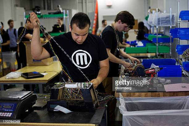 Employee Alex Morales assembles a Makerbot Industries LLC 3D Printer at the company's new factory in the Brooklyn borough of New York US on Thursday...