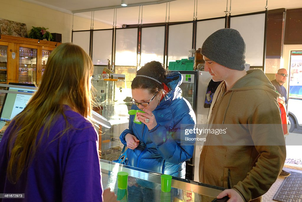 Employee Ashley Stanley, left, helps customers with their purchase of recreational marijuana inside the Evergreen Apothecary in Denver, Colorado, U.S., on Thursday, Jan. 9, 2014. Colorado has just legalized the commercial production, sale, and recreational use of marijuana, while Washington State will begin its own pot liberalization initiative at the end of February. On Jan. 8, New York Governor Andrew Cuomo said his state would join 20 others and the District of Columbia in allowing the drug for medical purposes. Photographer: Matthew Staver/Bloomberg via Getty Images