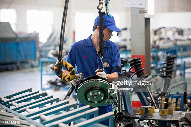 A employee assembles brake pads for BYD Co S6 sportutility vehicles at the company's assembly plant in Shenzhen China on Tuesday Aug 5 2014 Net debt...