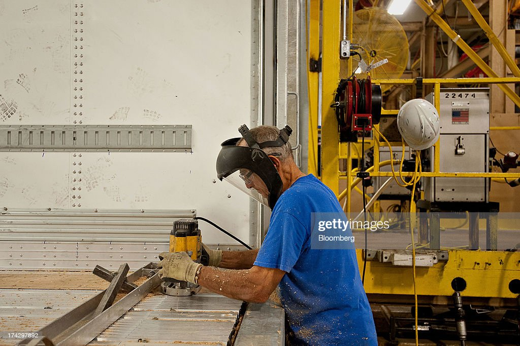 Employee Bob Serhal uses a router while preparing to install a kick plate inside the rear door of a semi trailer at the Wabash National Corp. facility in Lafayette, Indiana, U.S., on Monday, July 22, 2013. Wabash National Corp. is scheduled to release earnings figures on July 30. Photographer: Daniel Acker/Bloomberg via Getty Images