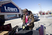 Employee Brad Bustle helps a customer with a chainsaw outside a Lowe's store in East Peoria Illinois US on Wednesday Feb 20 2013 Lowe's Cos the...