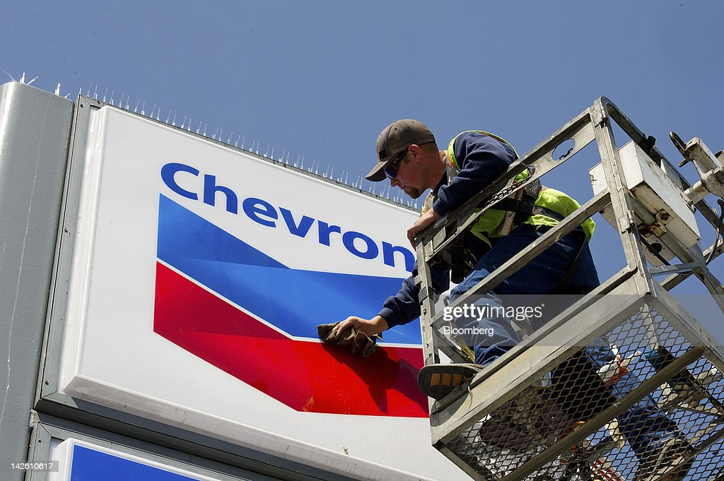 Employee Brandon Scully works on a Chevron Corp. sign at a gasoline station in San Francisco, California, U.S., on Friday, April 6, 2012. Gasoline slid to a four-week low as slower job growth in the U.S. and accelerating inflation in China raised concern that global demand for fuel may shrink. Photographer: David Paul Morris/Bloomberg via Getty Images