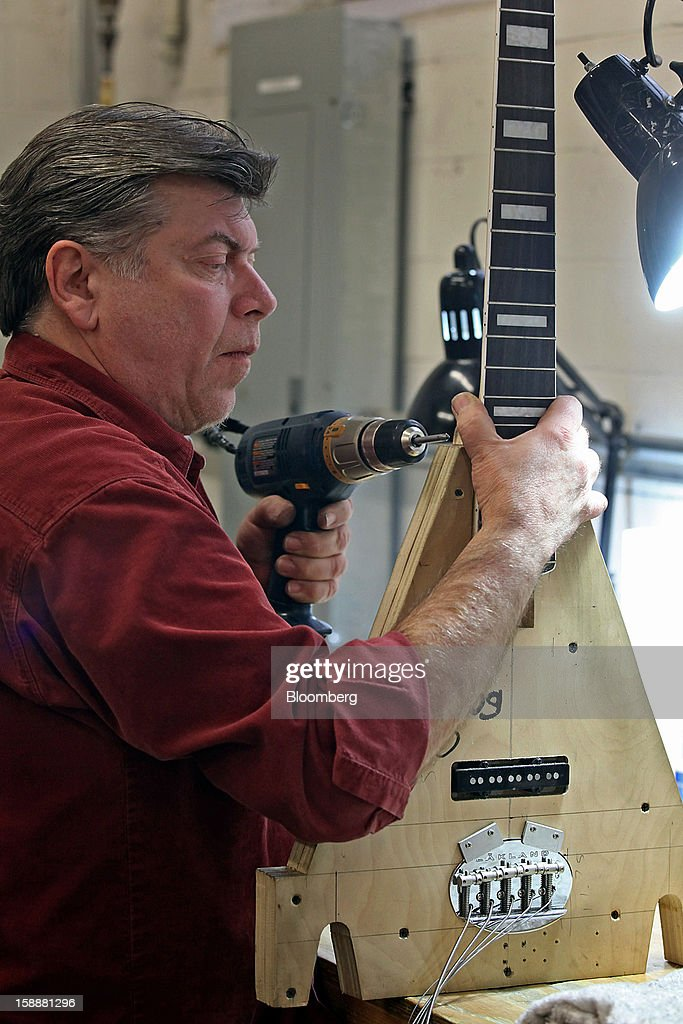 Employee Carl Pedigo sets up a Lakland bass guitar for a computerized fret dressing (PLEK) at the company's production facility in Chicago, Illinois, U.S., on Thursday, Dec. 27, 2012. Manufacturing picked up in December, reflecting growth in orders, employment and exports that indicate the U.S. expansion will be sustained in 2013 following the budget deal. Photographer: Tim Boyle/Bloomberg via Getty Images