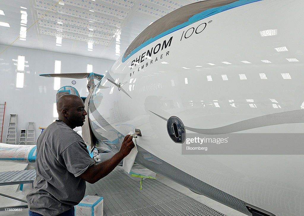 Employee Carlos Coleman polishes the fuselage of an Embraer SA Phenom 100 jet at the company's executive jet manufacturing facility in Melbourne, Florida, U.S., on Monday, July 15, 2013. Embraer SA, the world's largest manufacturer of commercial jets up to 120 seats, delivered 22 jets to the commercial aviation market and 29 to the executive aviation market, for a total of 51 aircraft in the second quarter of 2013, according to a company press release. Photographer: Mark Elias/Bloomberg via Getty Images