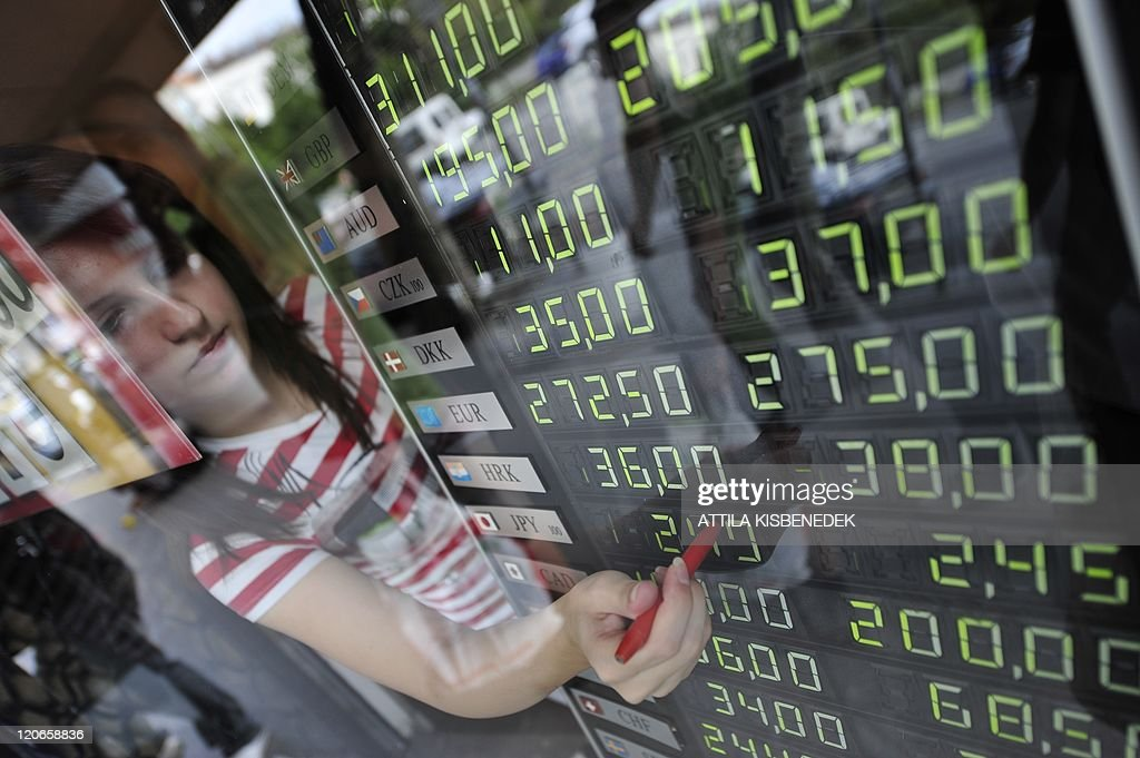 A employee changes currency rates on an information board at an exchange office in downtown Budapest on August 8 2011 as the combination of the US...