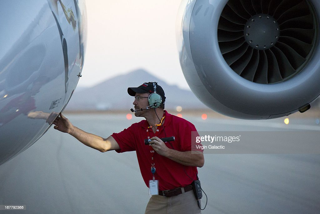 A TSC employee checks WK2 prior to the first powered flight of Virgin Galactic's SpaceShipTwo on April 29, 2013 in Mojave, California. SpaceShipTwo is a private enterprise aircraft, designed to carry paying passengers into space. The spacecraft was dropped from the mothership at high altitude and fired it's engine for a approximate 16-second burn taking the craft through the sound barrier. The hybrid rocket motor is fueled by nitrous oxide and a rubber propellent combination. The motor can be 'shut down' at any time for safety and flight requirement purposes.