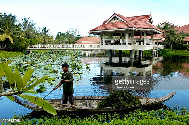 A employee cleans a pond at the Sofitel hotel in Siem Reap near the Angkor temples