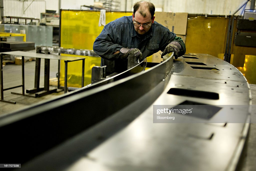 Employee Corey DeMoss assembles a railing assembly for an escalator at the Giese Manufacturing Co. in Dubuque, Iowa, U.S., on Thursday, Feb. 14, 2013. The U.S. Federal Reserve is schedule to release industrial productions figures on Feb. 15. Photographer: Daniel Acker/Bloomberg via Getty Images