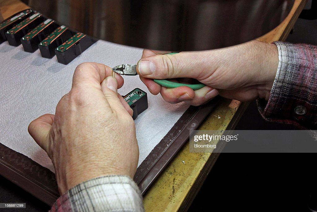 Employee Dave Schultz prepares to solder wire leads for a Lakland bass guitar pickup at the company's production facility in Chicago, Illinois, U.S., on Thursday, Dec. 27, 2012. Manufacturing picked up in December, reflecting growth in orders, employment and exports that indicate the U.S. expansion will be sustained in 2013 following the budget deal. Photographer: Tim Boyle/Bloomberg via Getty Images