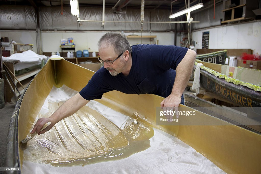 Employee Dave Tukua applies vinyl ester resin in order to laminate a foam core to the bottom of a composite canoe at the Wenonah Canoe factory in Winona, Minnesota, U.S., on Thursday, March 21, 2013. Wenonah Canoe, the second largest user of Kevlar fabric after the U.S. military, produces roughly 2500 canoes and 4000 kayaks each year. Photographer: Ariana Lindquist/Bloomberg via Getty Images