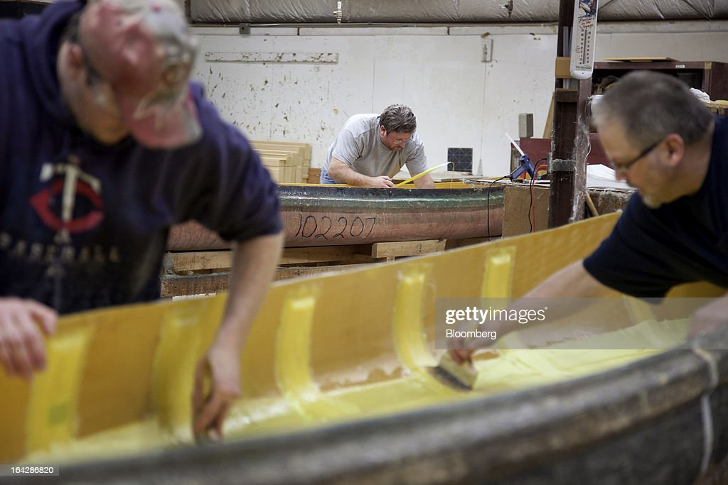 Employee Dave Tukua, right, and Shawn Peterson, left, apply vinyl ester resin in order to laminate a foam core to the bottom of a composite canoe while Doug Zwart works in the background at the Wenonah Canoe factory in Winona, Minnesota, U.S., on Thursday, March 21, 2013. Wenonah Canoe, the second largest user of Kevlar fabric after the U.S. military, produces roughly 2500 canoes and 4000 kayaks each year. Photographer: Ariana Lindquist/Bloomberg via Getty Images